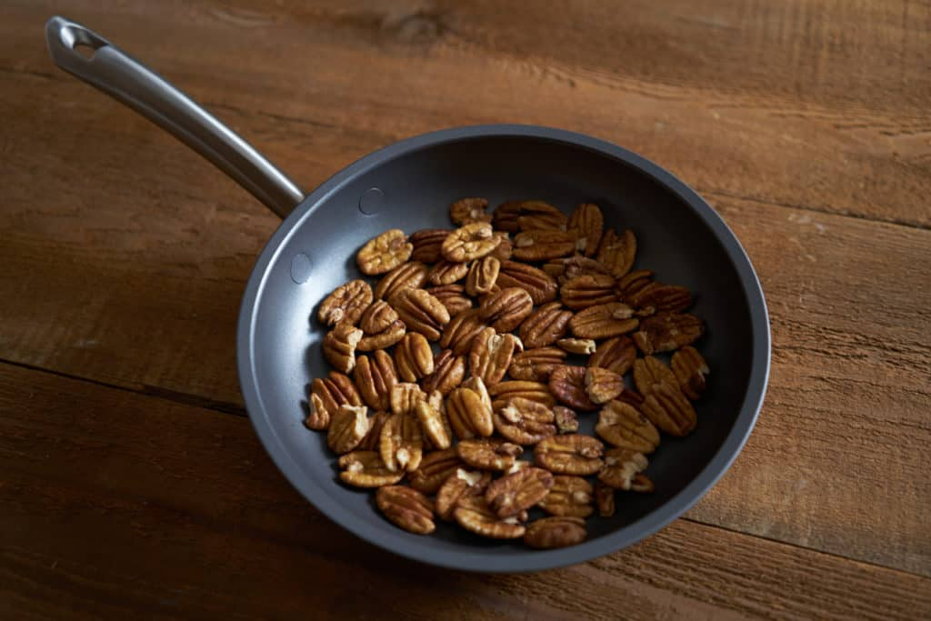 Pecan halves in a non stick skillet sitting on a wooden surface.