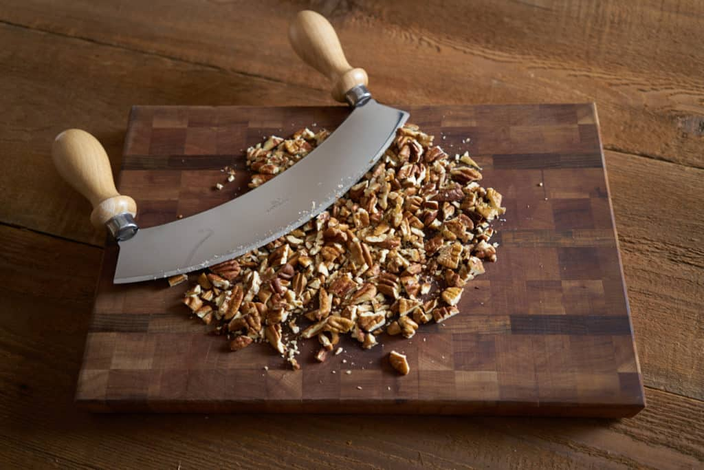 Chopped pecans and a mezzaluna on a wooden cutting board.