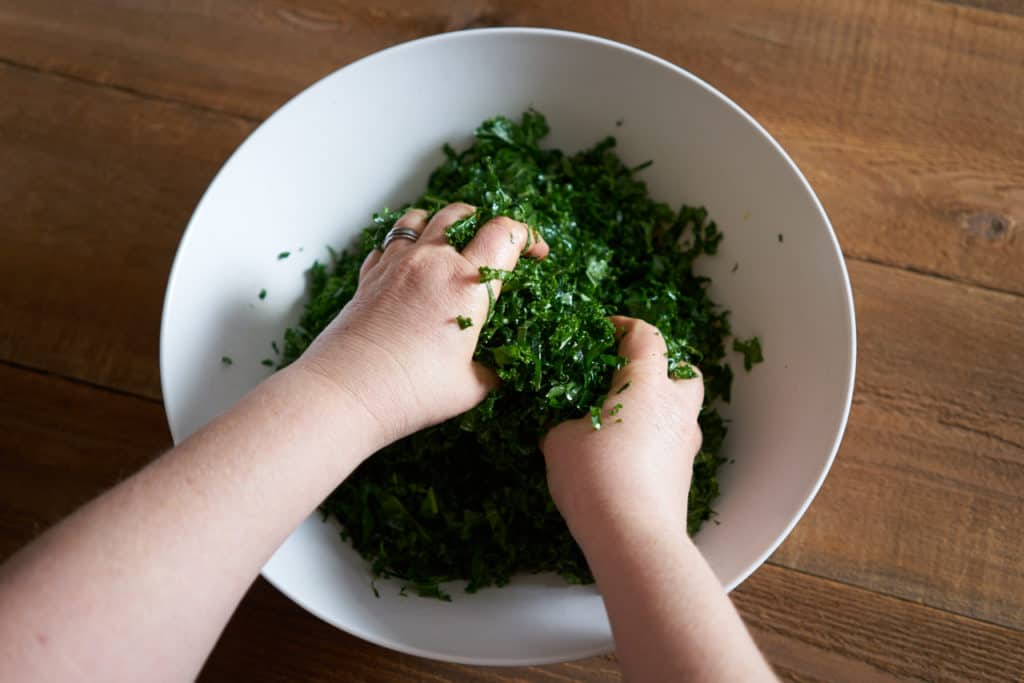 A woman's hands are shown massaging kale in a large white bowl.