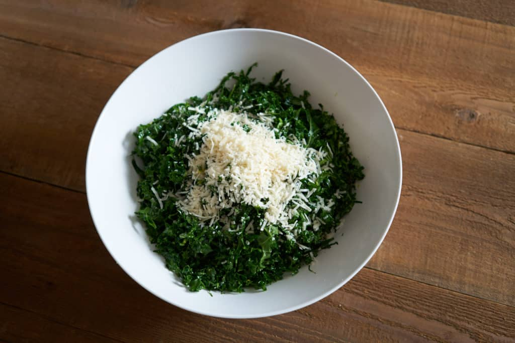 A large white bowl filled with massaged kale topped with grated parmigiano cheese.