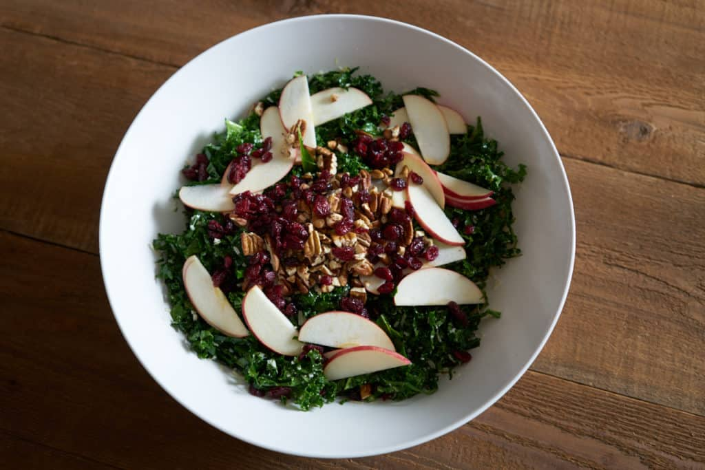 A large white bowl filled with massaged kale topped with grated parmigiano cheese, sliced apples, chopped pecans and dried cranberries.