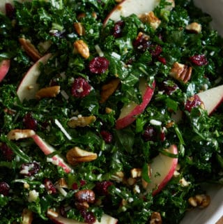 Kale salad with cranberries, apples and pecans in a white bowl on a wooden surface.