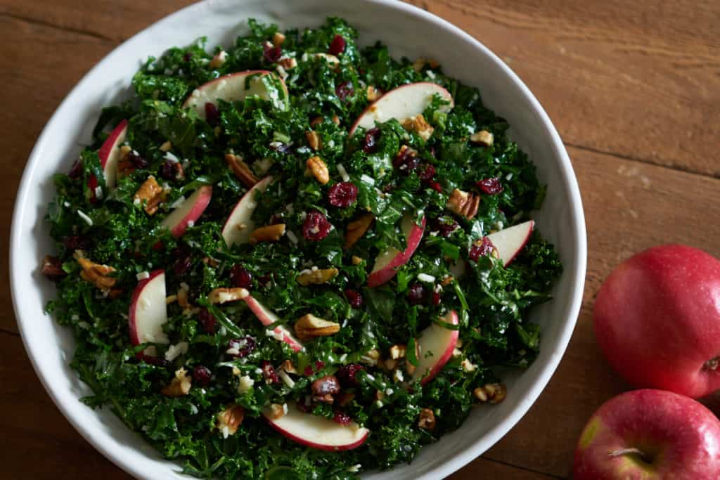 Kale salad with cranberries, apples and pecans in a white bowl on a wooden surface next to two red apples.