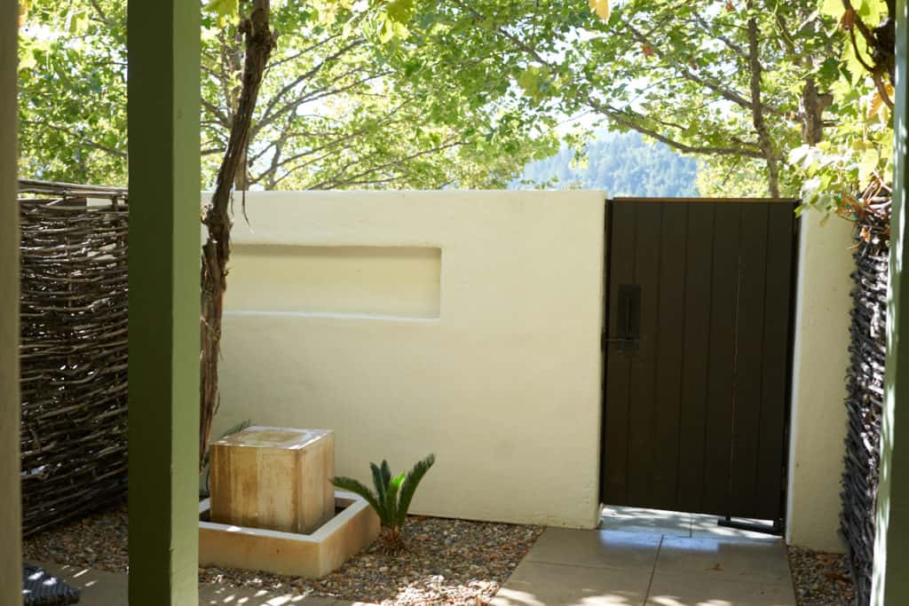 Private patio for one of the Lodge Rooms at Indian Springs, with a stucco wall a water feature, and a wooden gate.