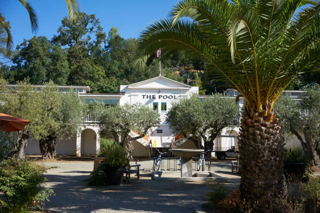 The Pool at Indian Springs, a white stucco building with an American flag on top, a fountain, palm trees and eucalyptus trees are in the foreground.