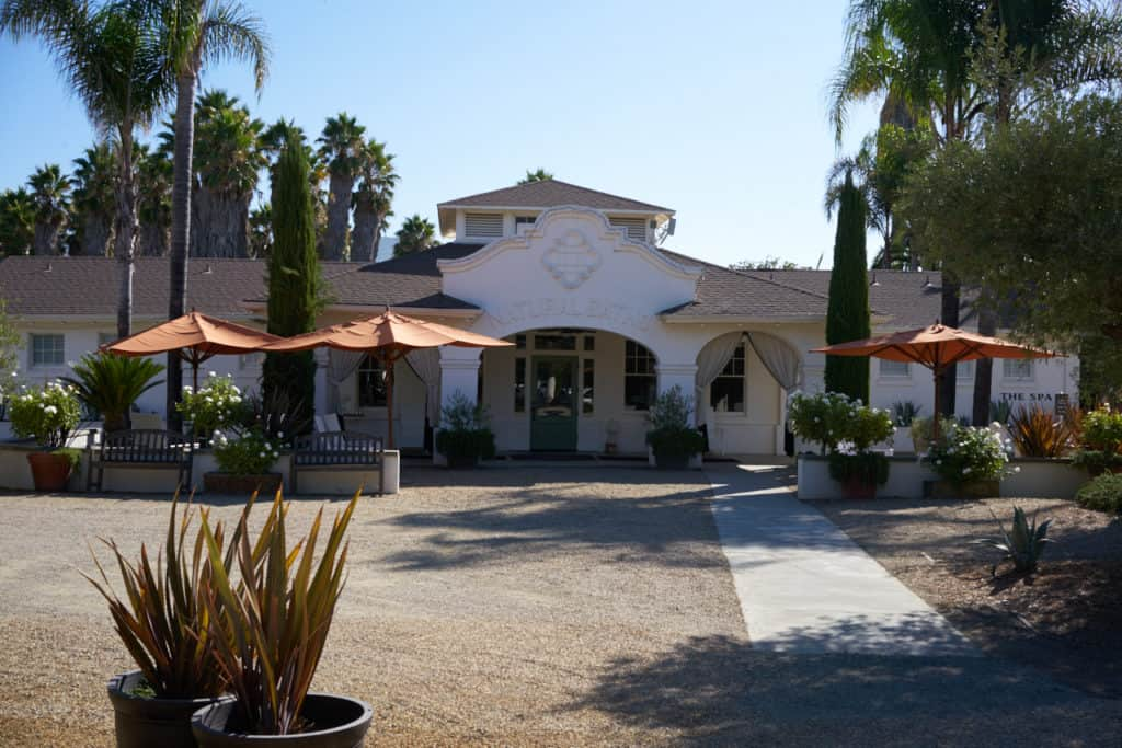 "A white stucco building with the wording ""Natural Baths"" over the arched entryway. Orange umbrellas and colorful plants are in the foreground."
