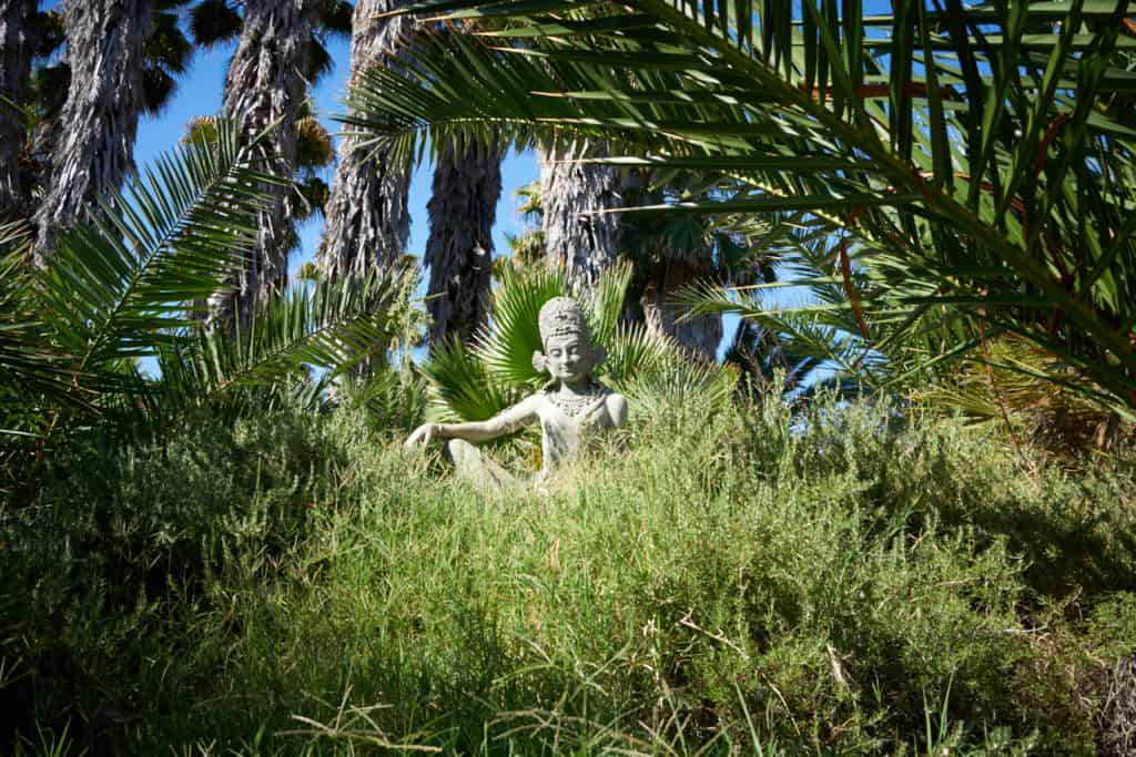 A bodhisattva statue surrouned by vegetation on the grounds of Indian Springs.