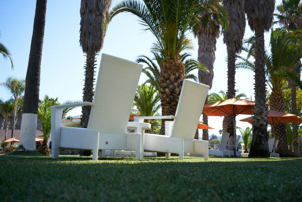 Two white lawn chairs surrounded by palm trees and orange umbrellas.