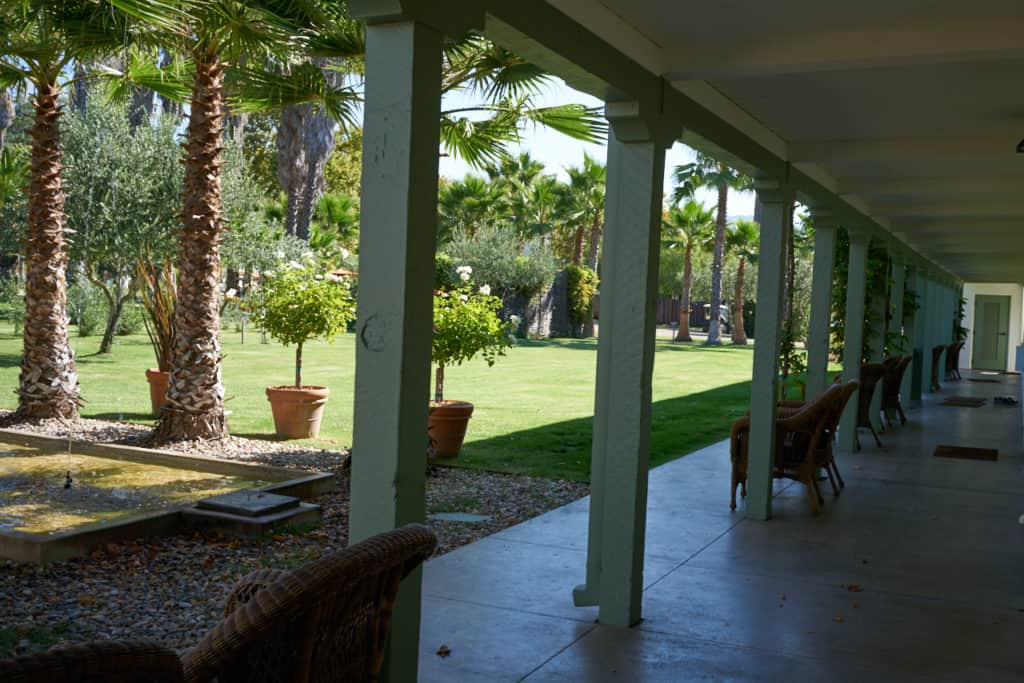 Underneath the portico of the Lodge Rooms, looking out toward a water feature, palm trees and a green lawn.