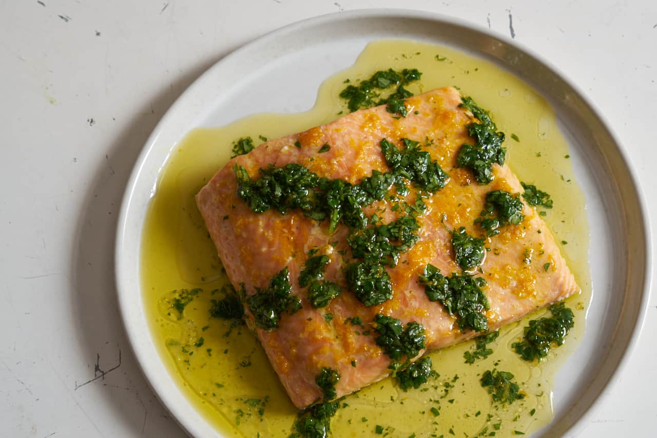 Oven roasted salmon with citrus salsa verde on a white plate. Olive oil and herbs surround the salmon filet.
