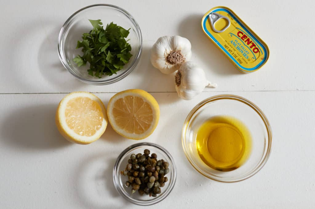 Olive oil, capers, parsley, garlic cloves, lemon halves and a tin of anchovies on a white surface.