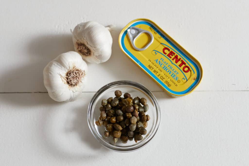 Capers in a small bowl, two cloves of garlic, and a tin of anchovies on a white surface.