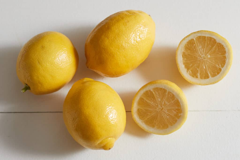 Three whole lemons and one lemon cut in half on a white surface.