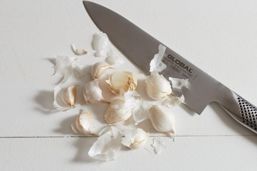 A chef's knife and several garlic cloves on a white surface.