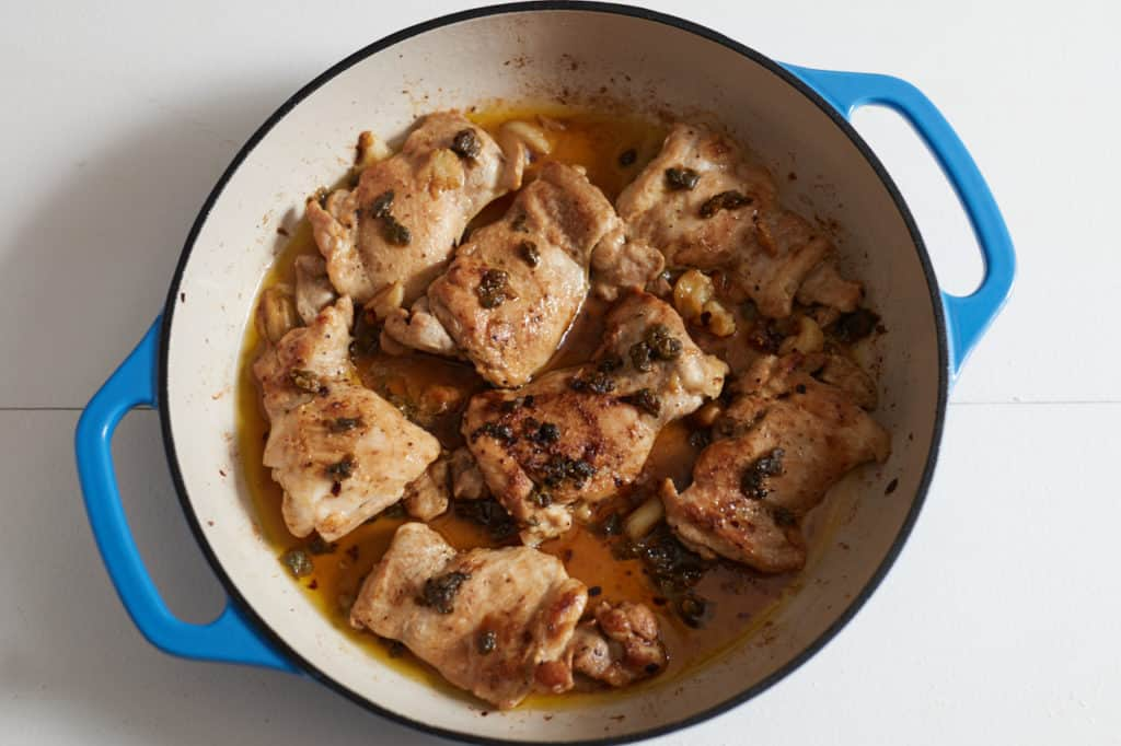 Cooked boneless, skinless chicken thighs in a blue casserole dish with capers and garlic.