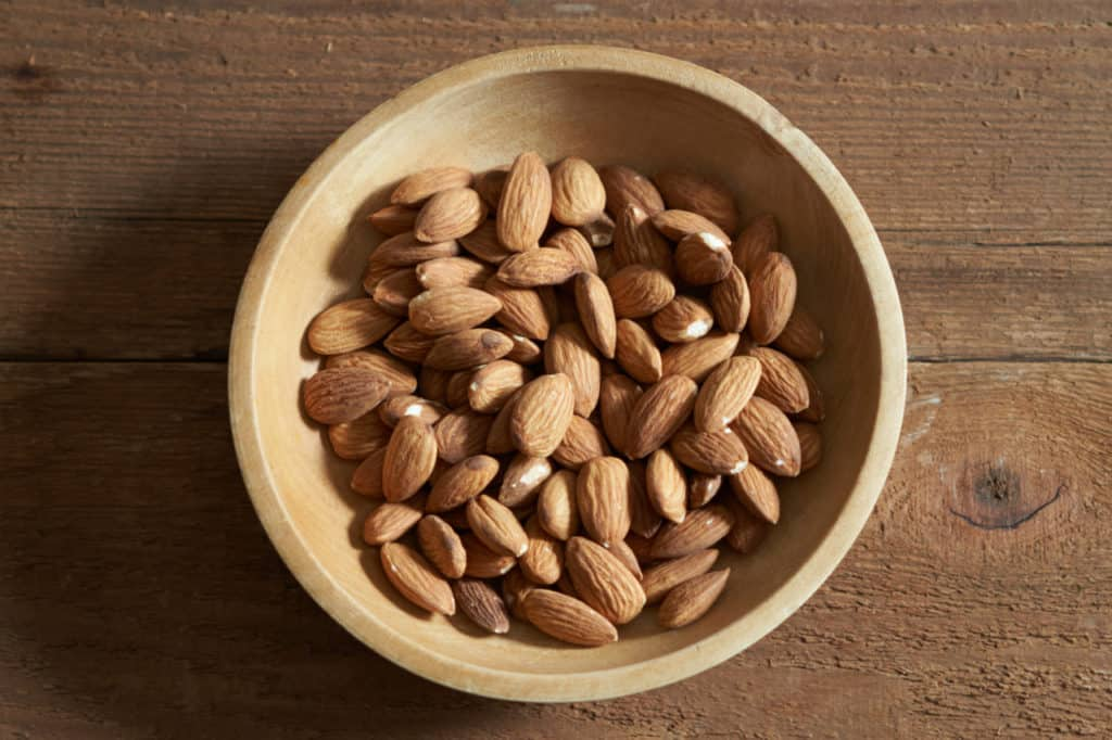 Whole almonds in a small wooden bowl.