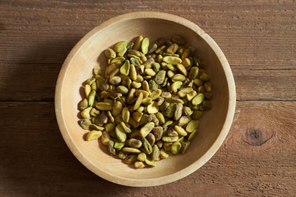 Whole pistachios in a small wooden bowl.