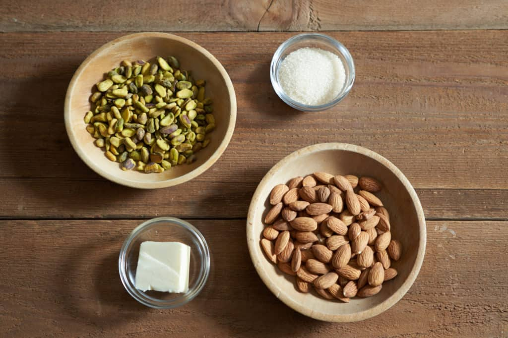 Two small wooden bowls with almonds and pistachios, and two small glass bowls with sugar and butter.