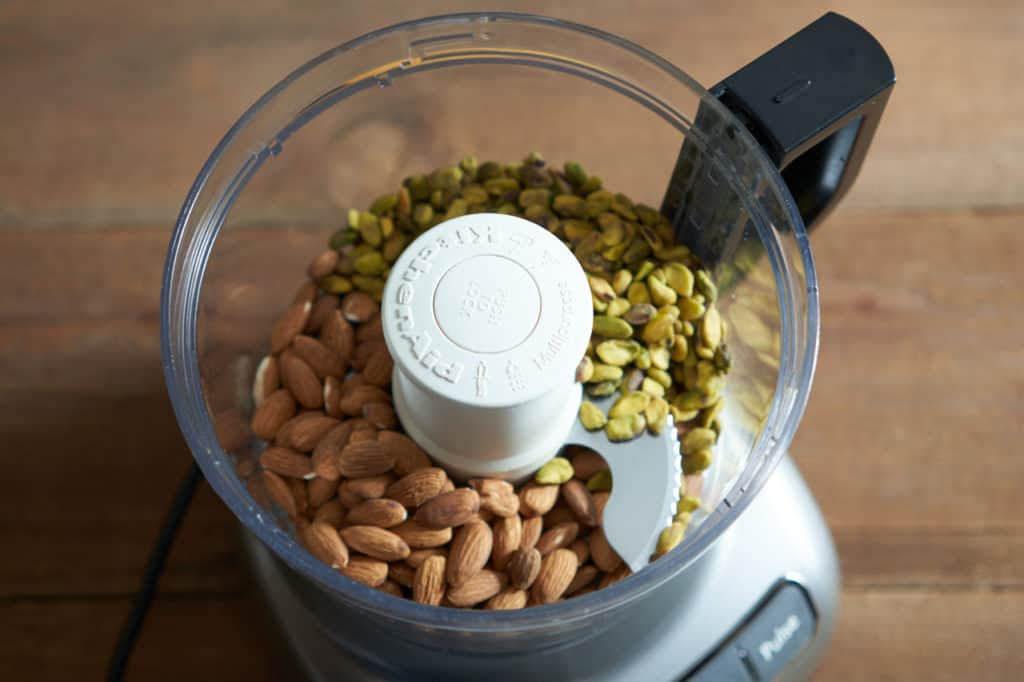 A food processor containing whole pistachios and almonds.