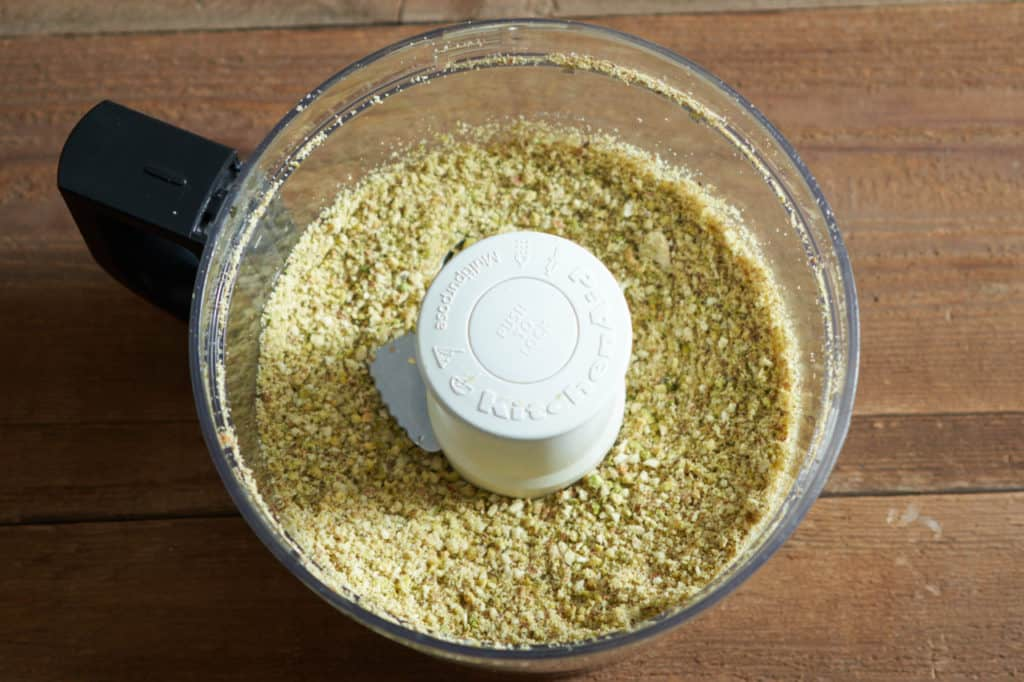 A food processor with ground pistachios and almonds.