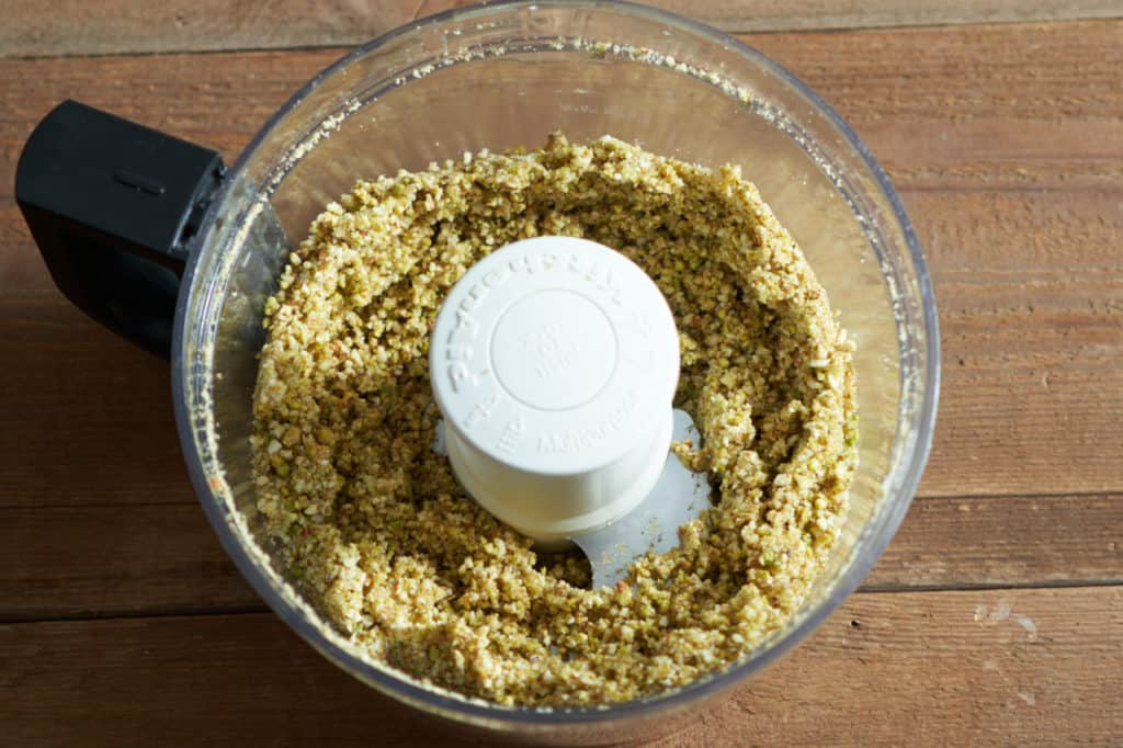 A food processor with ground pistachios, almonds, sugar and butter.