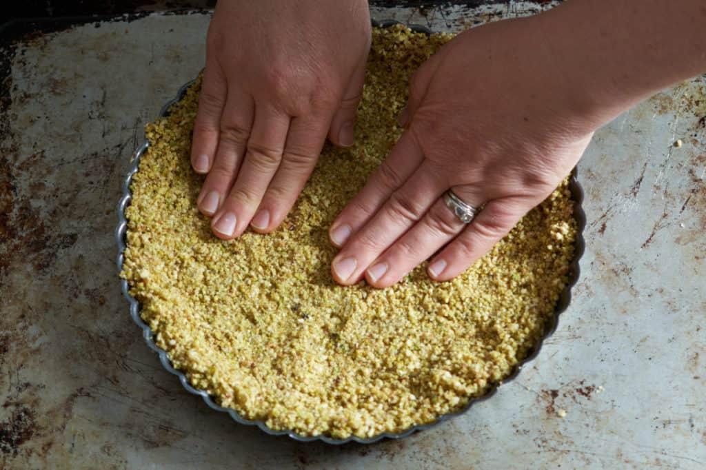A woman's hands pressing tart crust into a pan.