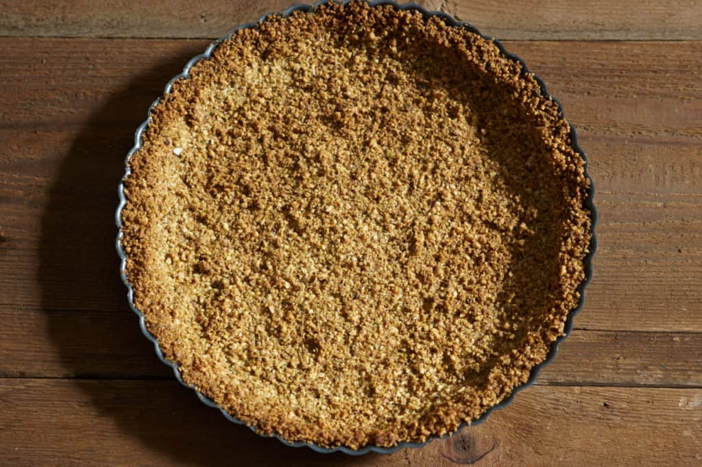 Baked gluten free tart crust cooling on a table.