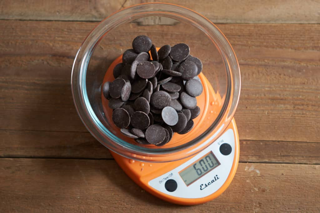 A bowl of dark chocolate baking discs in a glass bowl on a kitchen scale.