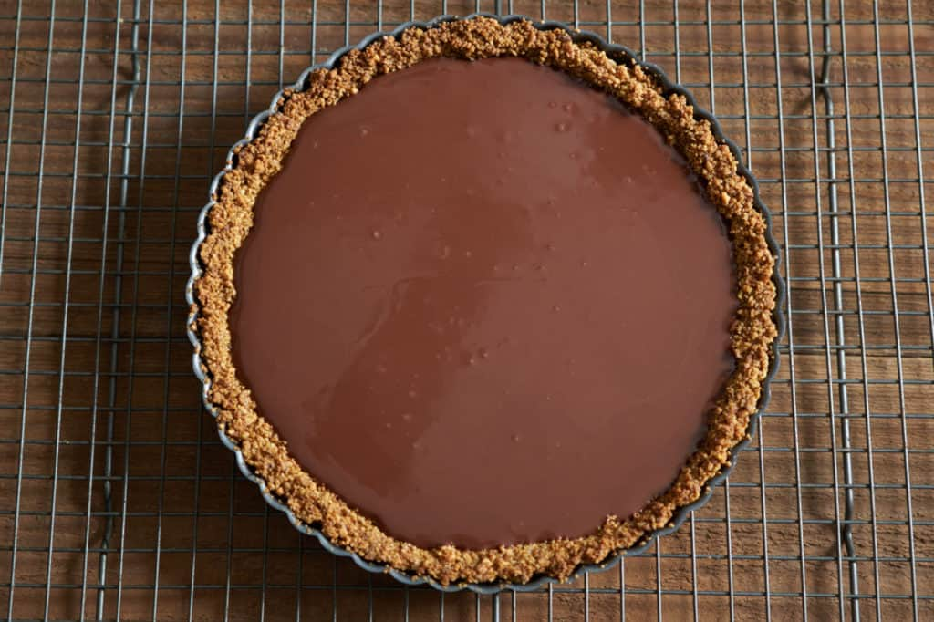 Baked gluten free tart crust filled with melted chocolate ready for chilling in the fridge.