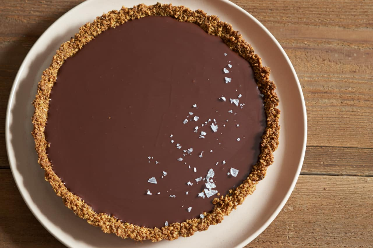 Gluten free chocolate tart topped with sea salt flakes on a pink plate.
