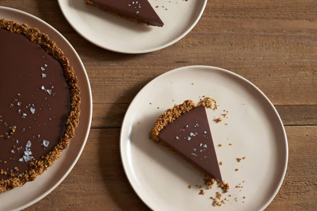 Slices gluten free chocolate tart topped with sea salt flakes on pink plates.