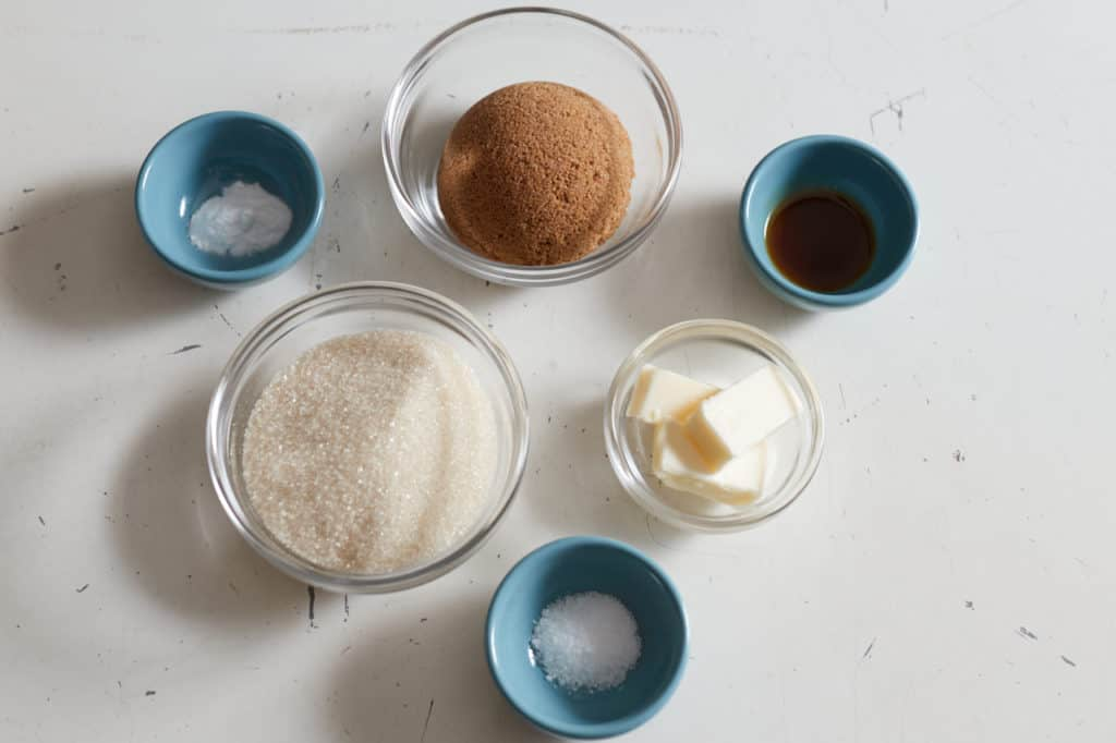 Small blue and glass bowls with ingredients for chocolate chip cookies.