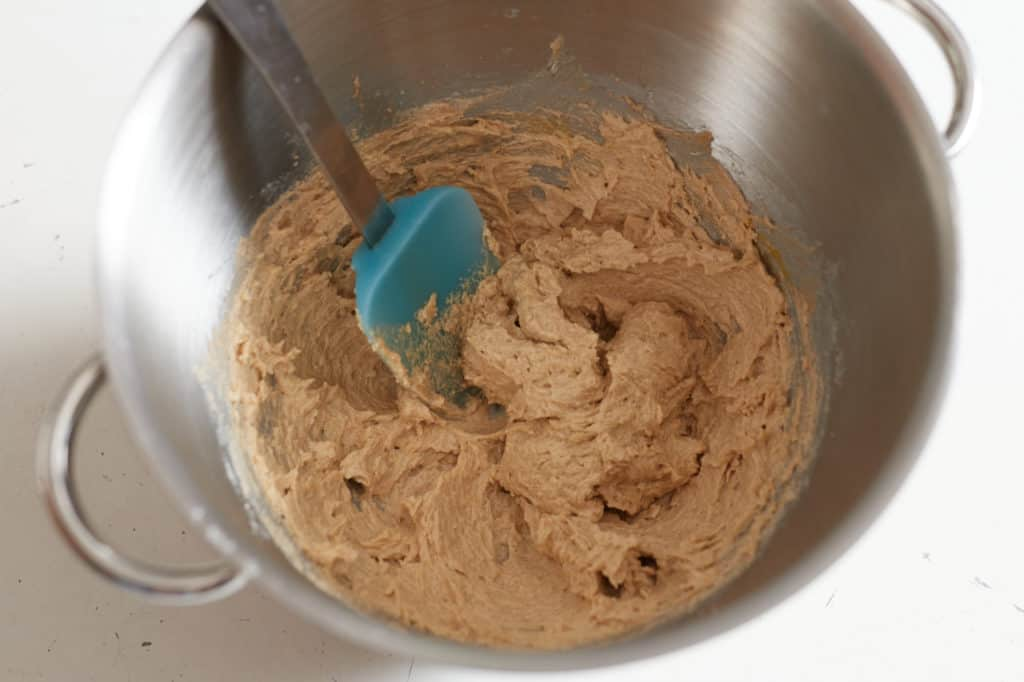 A blue spatula sits in a metal mixing bowl with creamed butter and sugar.