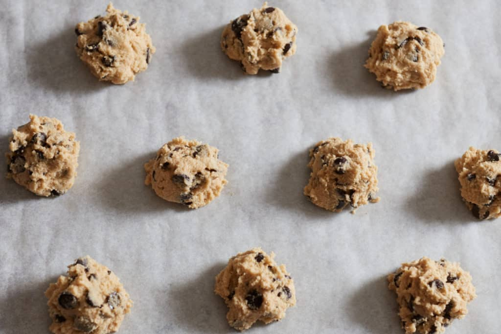 Gluten free chocolate chip cookie batter formed into balls on parchment paper, ready for baking.