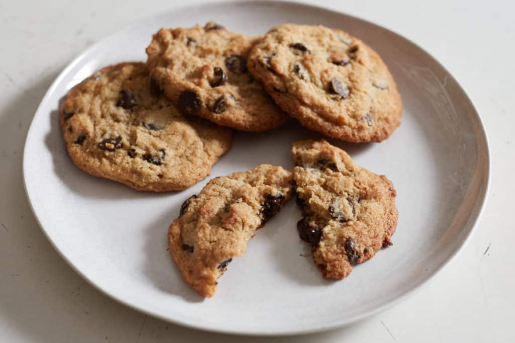 Gluten free chocolate chip cookies on a white plate, one is broken in half.
