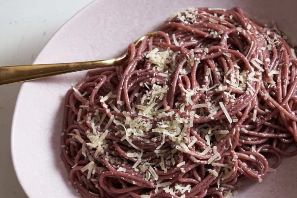 A gold spoon in a pink bowl filled with red wine spaghetti topped with parmigiano cheese.