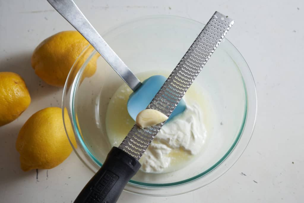 A microplane grater with a clove of garlic sits across glass bowl of yogurt and lemon juice next to three lemons.