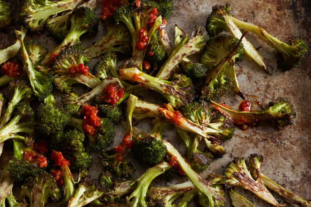 Charred broccoli on a sheet pan drizzled with Calabrian chili paste.