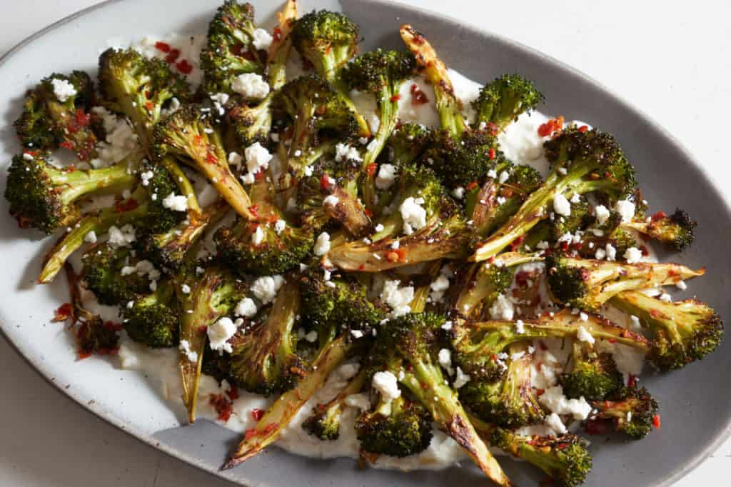 Charred broccoli with Calabrian chili paste on a grey and white platter.