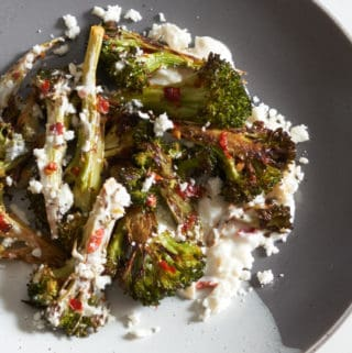 Charred broccoli with Calabrian chili paste on a grey and white plate.