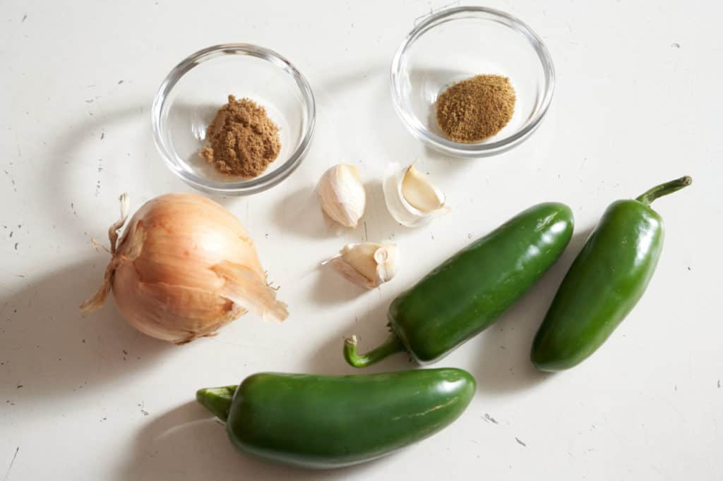 Jalapeño peppers, an onion, three garlic cloves, and two small glass bowls with spices.