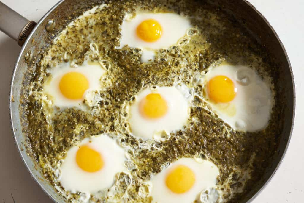 Six cooked sunny-side up eggs in green shakshuka sauce in a large skillet.