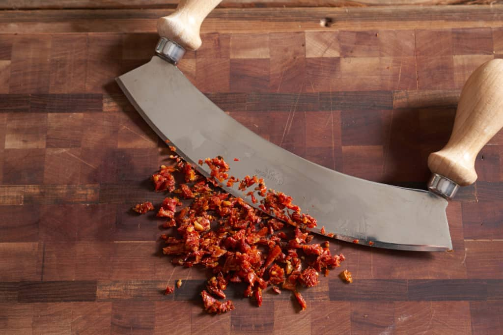 A mezzaluna on a cutting board with diced sun-dried tomatoes.
