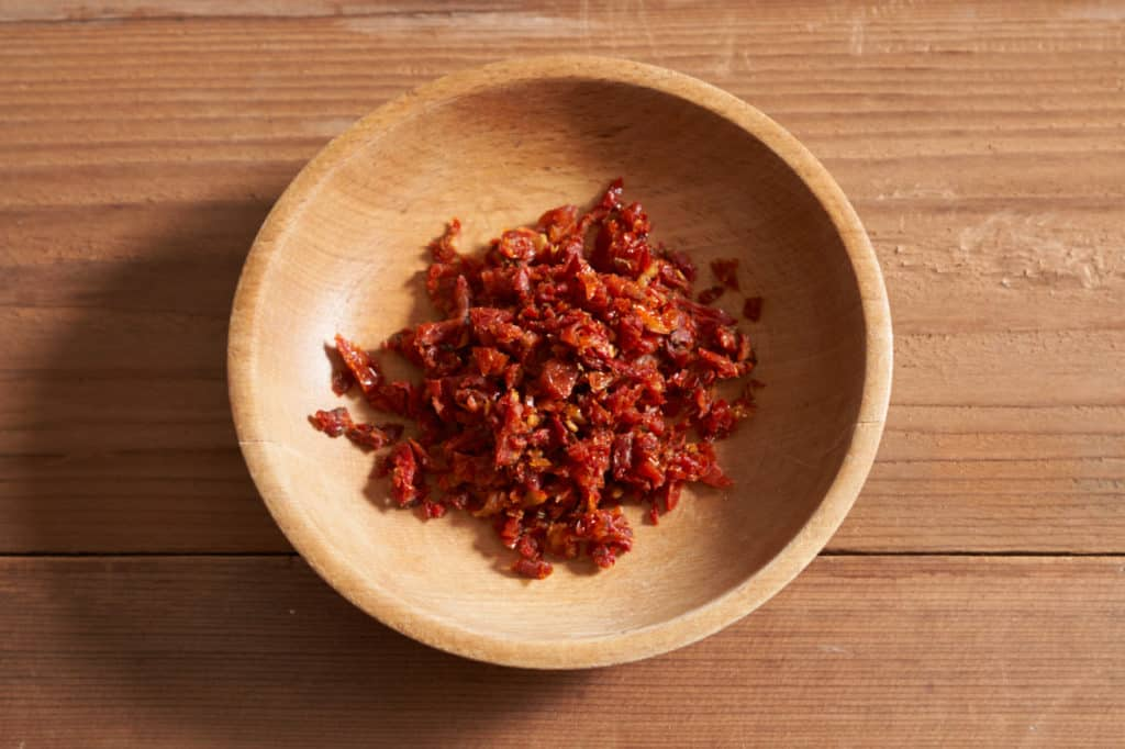 A wooden bowl of diced sun-dried tomatoes.