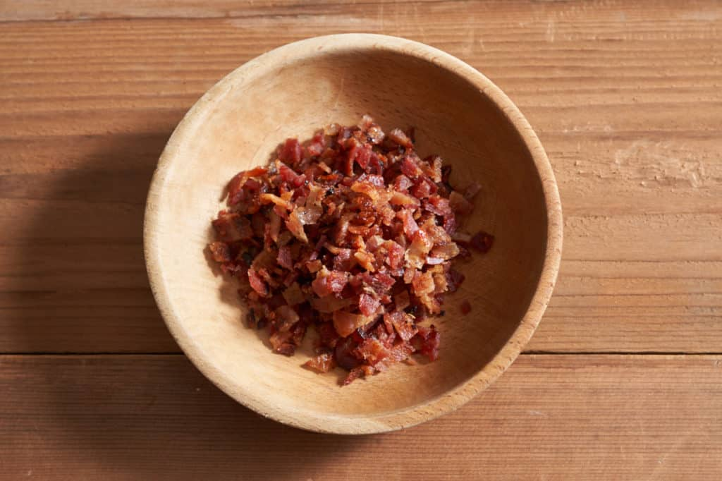 A wooden bowl of diced bacon.
