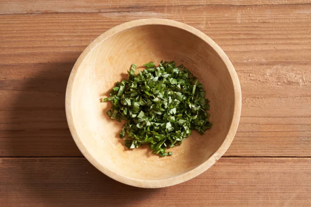 A wooden bowl of chopped basil.