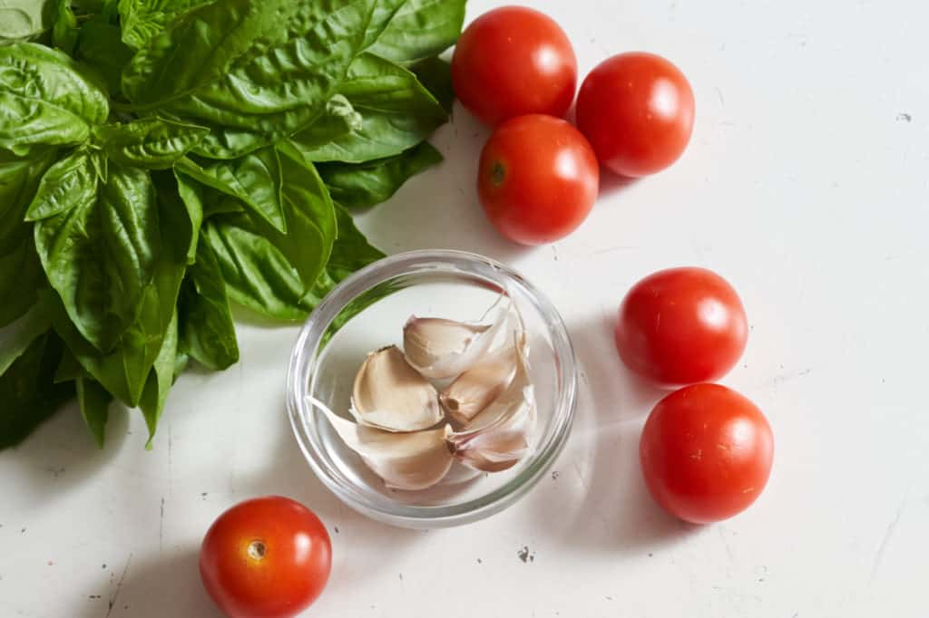 Fresh basil, cherry tomatoes and a small glass bowl filled with garlic cloves.
