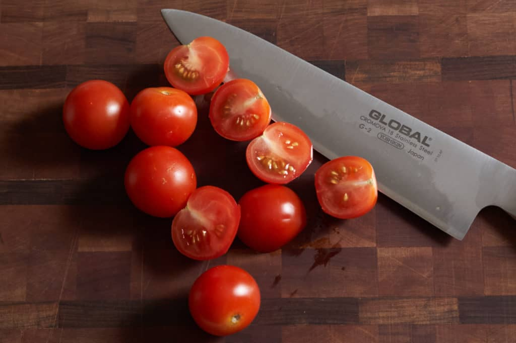 A chef's knife on a cutting board with sliced cherry tomatoes.