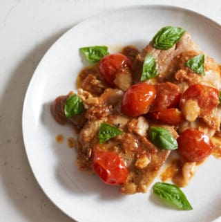 Chicken thighs with cherry tomatoes and fresh basil on a white plate.