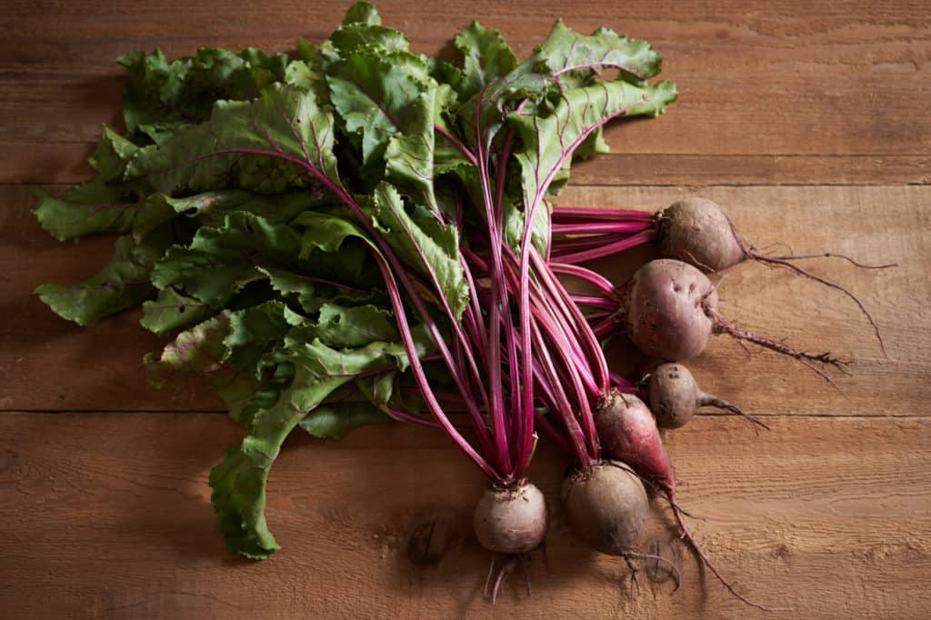 A bunch of freshly picked beets with their greens on a wooden surface.